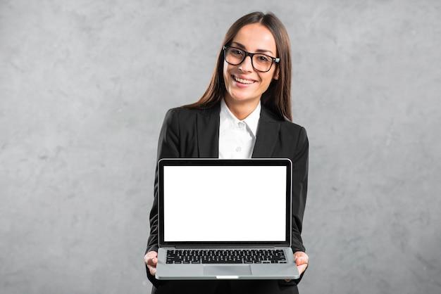 空白の白い画面表示を持つラップトップを示す笑みを浮かべて若い実業家の肖像画