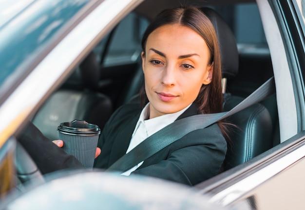使い捨てのコーヒーカップを保持している車の座席の中に座っている女性実業家