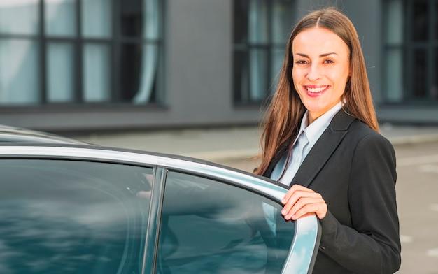 Портрет счастливой молодой коммерсантки стоя близко открытая автомобильная дверь