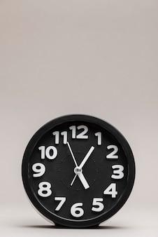 無地の背景に黒の目覚まし時計のクローズアップ