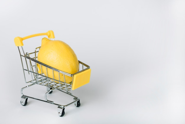 白い背景の上のショッピングカートに黄色いレモンのクローズアップ