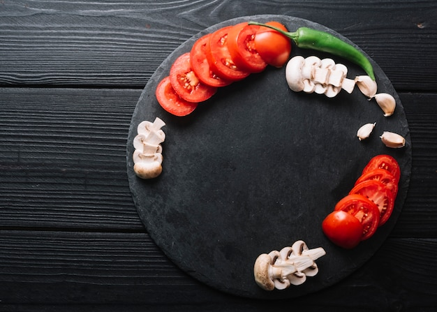 Зеленый перец чили; зубчики чеснока с ломтиками грибов и помидоров на черной деревянной поверхности
