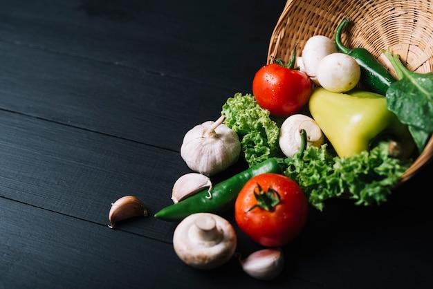 黒い木製の背景に枝編み細工品バスケットと新鮮な生野菜