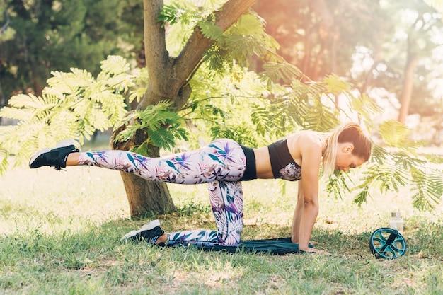 公園の木の下に伸びる若い女性の側面図