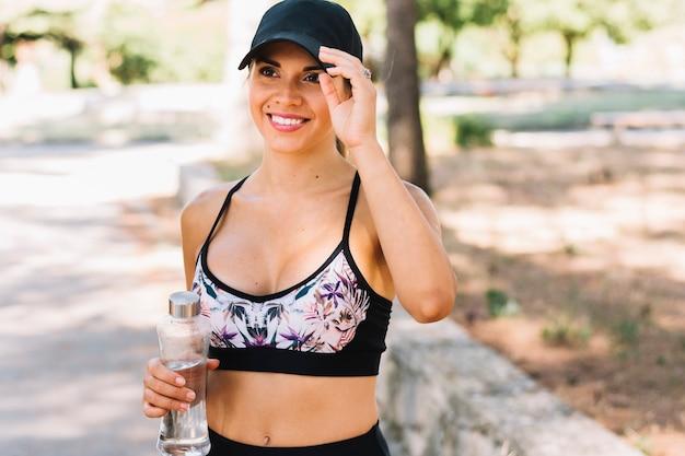 プラスチック製の水ボトルを保持している黒い帽子を着て笑顔のスポーティーな若い女性の肖像