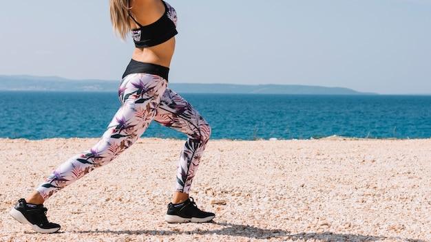 ビーチの近くで脚を伸ばしている女性の低い部分