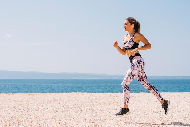 ビーチで走っている若い女性の側面図
