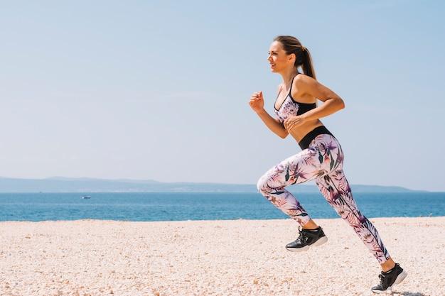 青い空に対してビーチの近くでジョギングする若い女性に笑顔