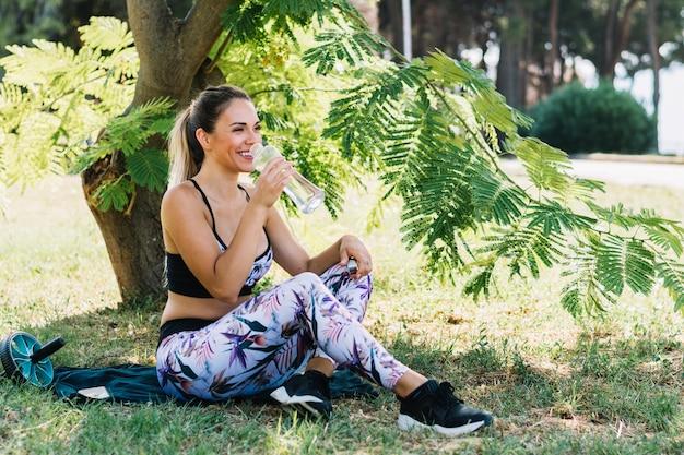 庭でびんから飲み水を楽しむ釣りの若い女性