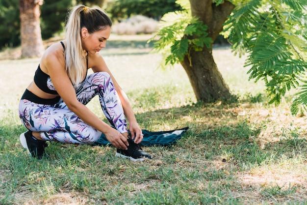 庭で彼女の靴ひもを結ぶ健康な若い女性