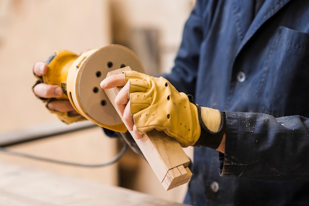 木製のブロックをサンダーでサンディングする男性の大工のクローズアップ