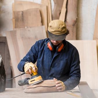 木製のブロックを滑らかにするためにサンダーを使用して彼の首の周りに耳の防衛を持つ男のクローズアップ