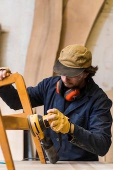 ワークベンチで電動工具で家具を研磨している男性の大工のクローズアップ