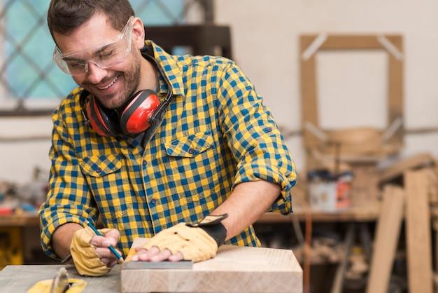 彼のワークショップで木材で働く若い男性の大工笑顔