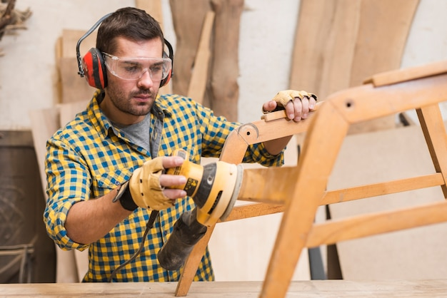 ワークショップ、木製家具をサンディングするハンディーのクローズアップ