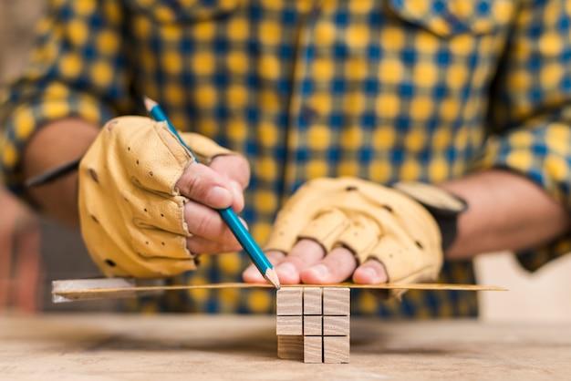Конец-вверх руки мужского плотника делая измерение на деревянном блоке