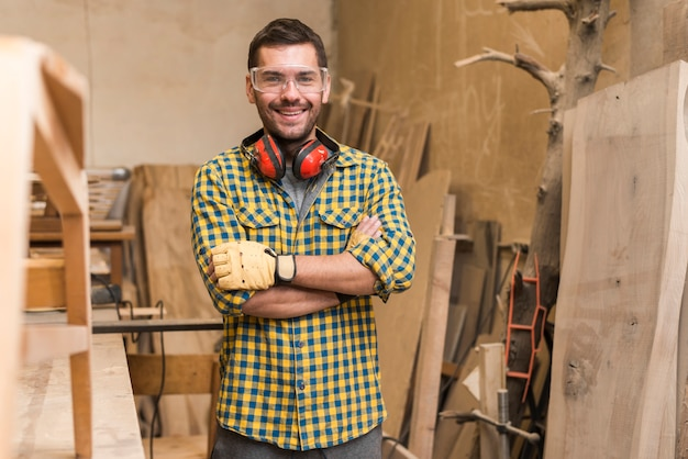 ワークショップで彼の腕を持つ自信を持って幸せな大工が立っていた