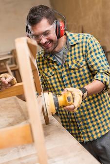 ワークベンチ上の木材のための電気サンダーを使用して男性の大工を笑顔
