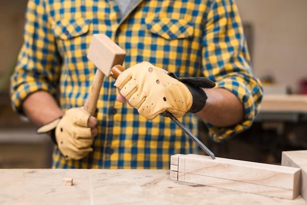 Средняя часть плотника мужского пола, ударяющего долотом с молотком на прямоугольном блоке