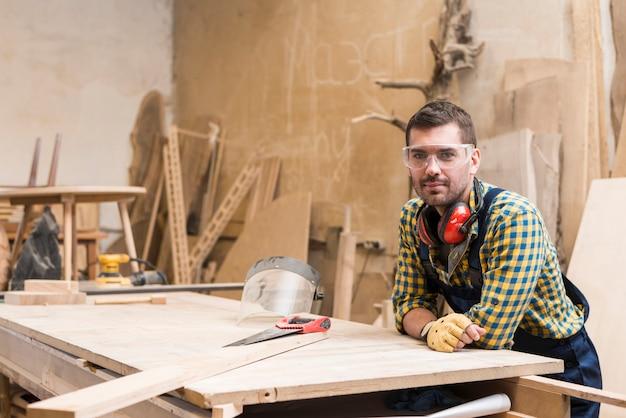 ワークショップのワークベンチに傾いている男性の大工の肖像