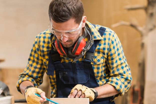 ワークショップで働く安全メガネを着用している男性の大工のクローズアップ