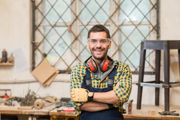 Портрет улыбающегося мужского плотника, стоя перед верстаком