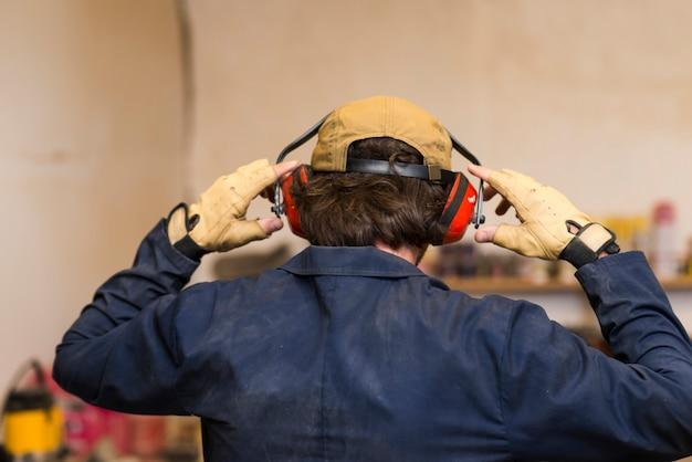 彼の耳の上に耳の防衛を着ているハンディーマンのリアビュー