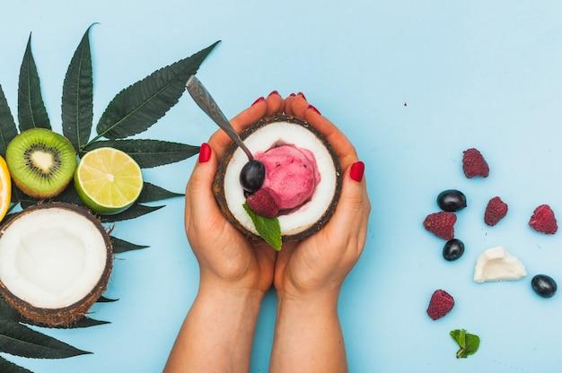 青い背景に冷凍アイスクリームとココナッツを保持して女性の手のオーバーヘッドビュー
