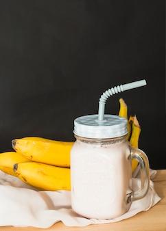 黒の背景に木製のテーブルの上に白い服の上に黄色のバナナとバナナスムージー