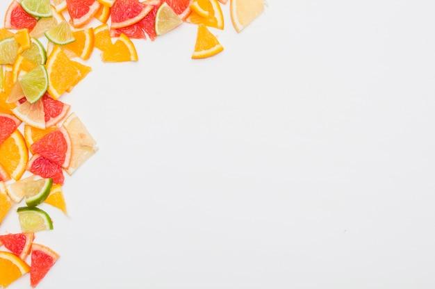 白い背景の角にカラフルな柑橘類のスライス