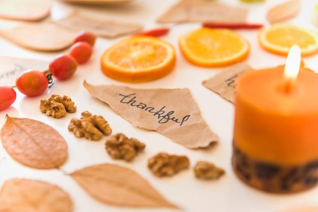ノート、果物、葉の近くにキャンドルを燃やす