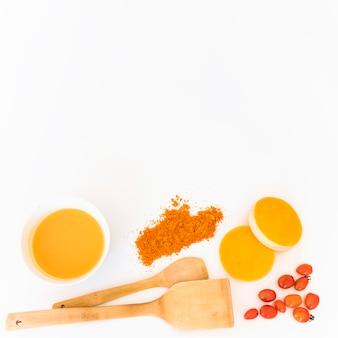 Лоскуты рядом с томатами, перцем и оранжевой жидкостью