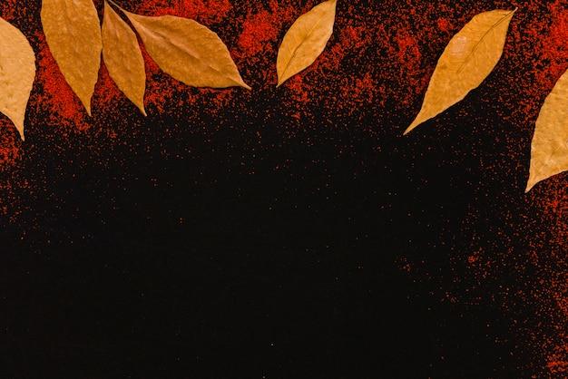 Листья между перцем на темной доске