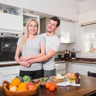 多くのカラフルな野菜とテーブルの後ろに立って笑顔の若いカップルの肖像