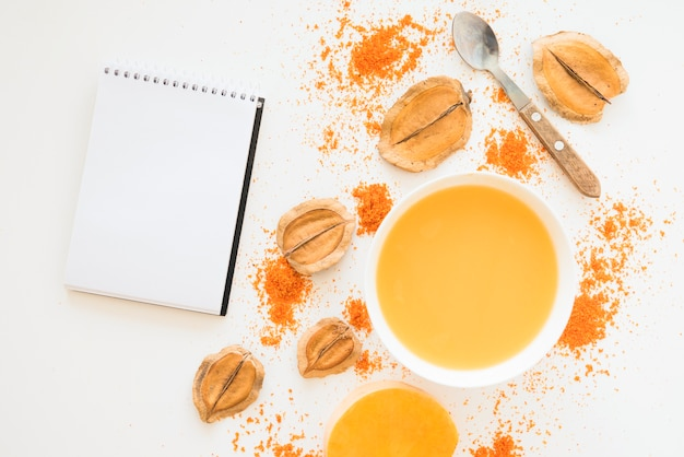 Ноутбук возле листвы перца и оранжевой жидкости