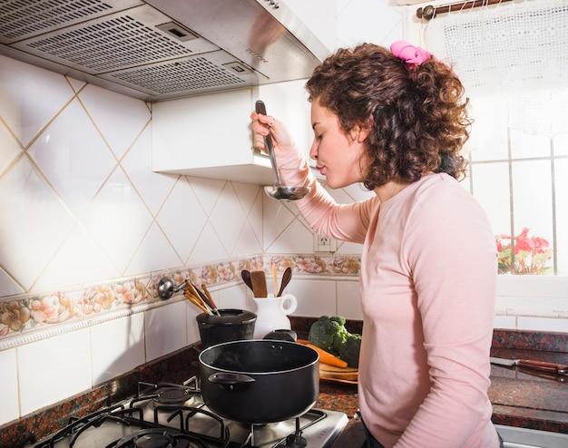 Вид сбоку молодой женщины, дегустация супа из ковша на кухне