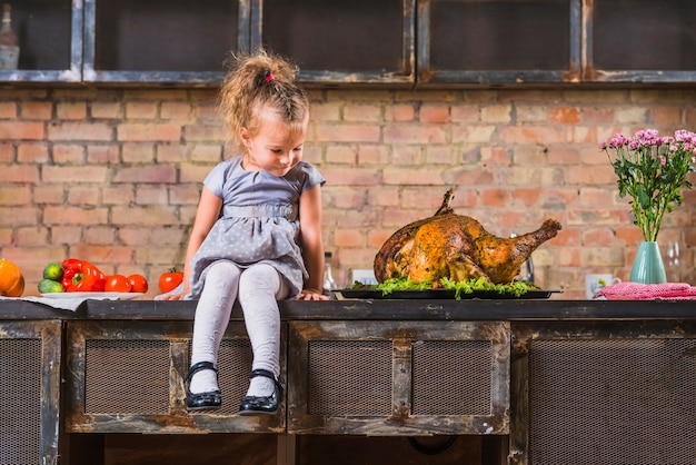 Маленькая девочка, сидя на столе с испеченной индейкой