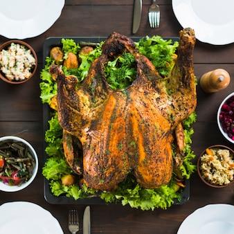 テーブルにサラダがある焼きたての七面鳥