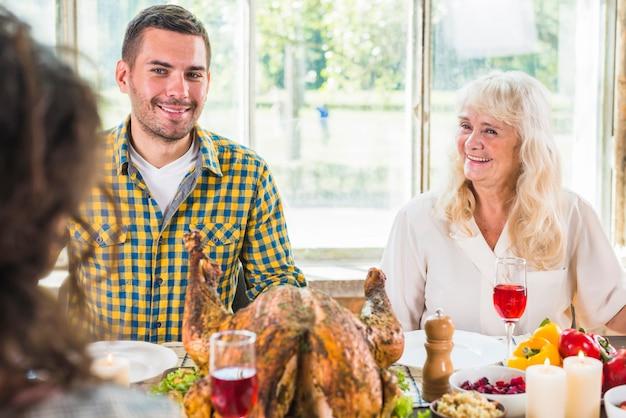 Мужчина и старуха улыбается женщина сидит за столом