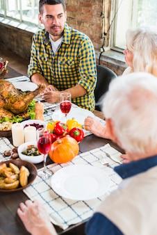 Человек, сидящий за столом возле пожилой женщины и мужчины