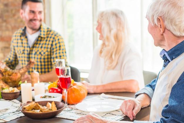 年配の女性と男性の近くのテーブルに座っている笑顔の男