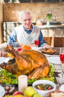 Пожилой мужчина сидит за столом с едой