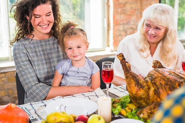 老婦人の近くのテーブルで子供と一緒に座って笑顔の女性