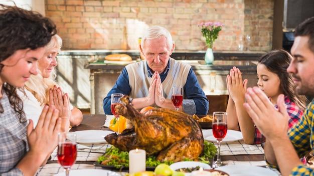 食べる前にテーブルで祈る家族