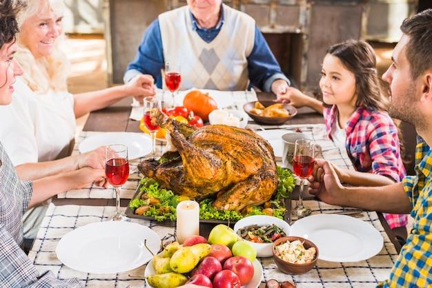 テーブルで手をつないでいる幸せな家族