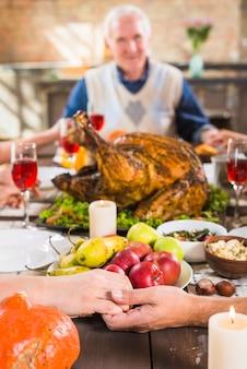 人間の手は、老人の近くの食べ物でテーブルに手を置く