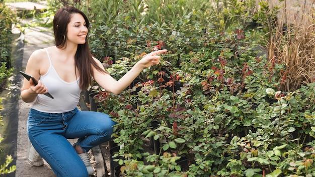庭の植物を指差しで手にデジタルタブレットを保持している笑顔の若い女性