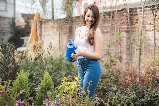 美しい若い女性は、植物に水を庭に立って