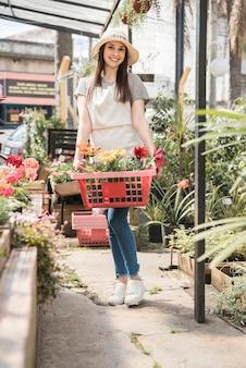 カメラを見て美しい花のトレイで幸せな女性の肖像画