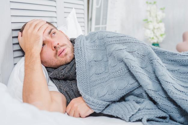 頭痛とベッドの上に横たわっている若い男と、彼の額に触れる熱